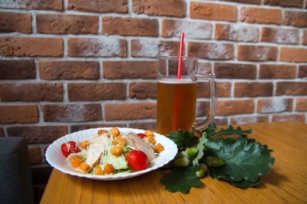 Um litro de cerveja com canudo e uma salada césar. no fundo de um bar pub de parede de tijolos