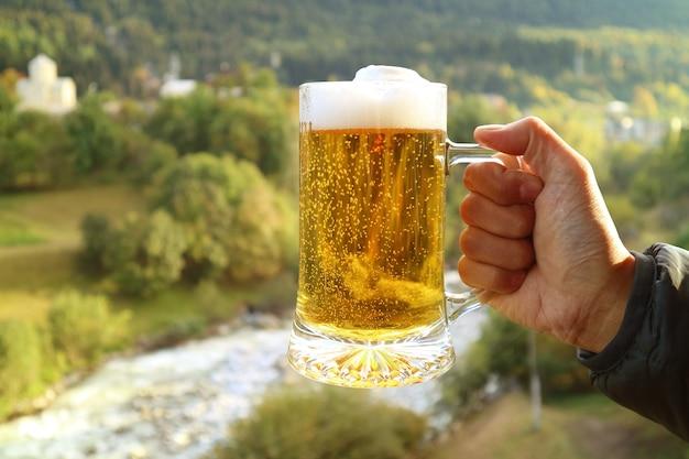 Um litro de cerveja na mão de um homem contra a vista desfocada do sopé da floresta ao sol da tarde