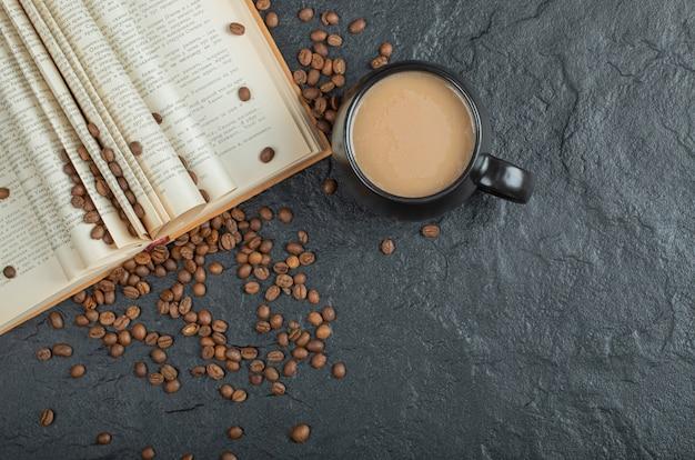 Um livro aberto com grãos de café em um fundo cinza.