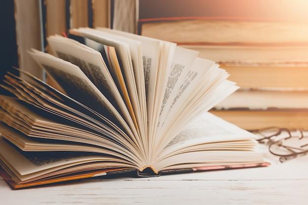 Um livro aberto com vidros em uma tabela de madeira na perspectiva de um grupo de livros, tonificação do vintage.