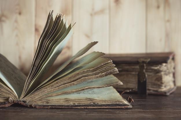 Um livro aberto muito antigo com páginas amareladas na mesa de madeira.
