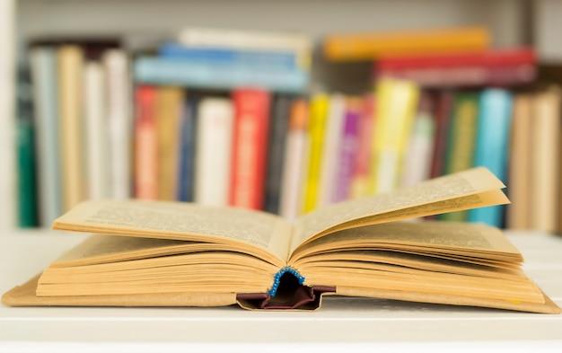 Um livro aberto no fundo de uma prateleira com livros.