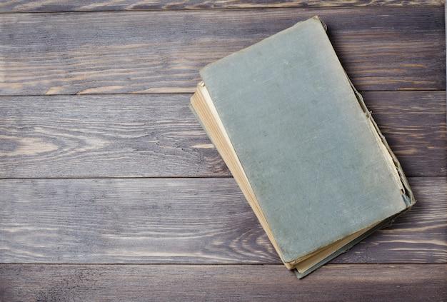 Um livro antigo com a capa rasgada. fundo de madeira. vista superior plana. espaço para texto