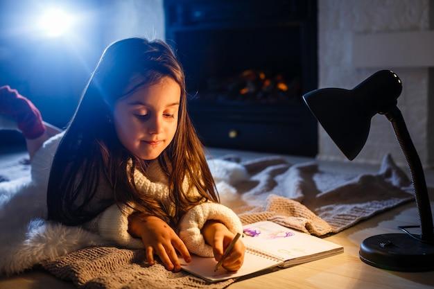 Um livro bonito da menina no assoalho sob a lâmpada. crianças e educação.