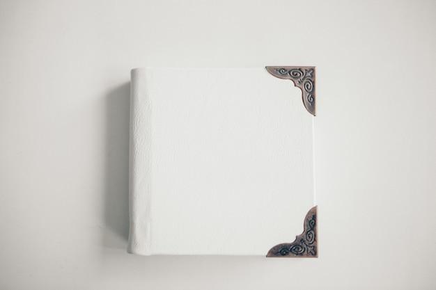 Um livro branco embrulhado em couro em um fundo branco. álbum de fotos com moldura de metal. cartão de felicitações