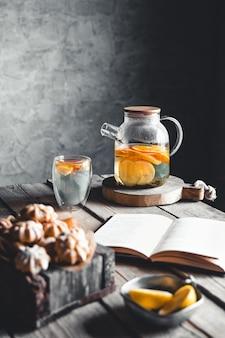 Um livro com chá de frutas cítricas está esperando em uma cozinha vintage. descansar, passatempos, educação, ler.