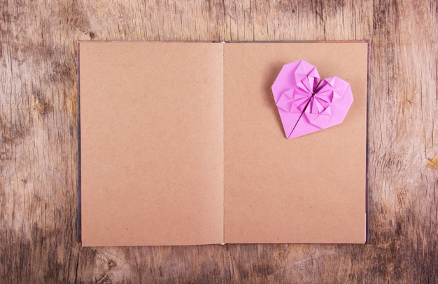 Um livro com páginas em branco e um coração de origami em um fundo de madeira. coração violeta feito de papel e diário. copie o espaço