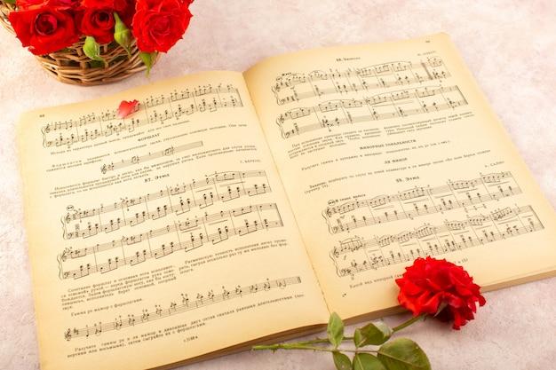 Um livro de notas musicais com vista superior aberto junto com rosas vermelhas em rosa
