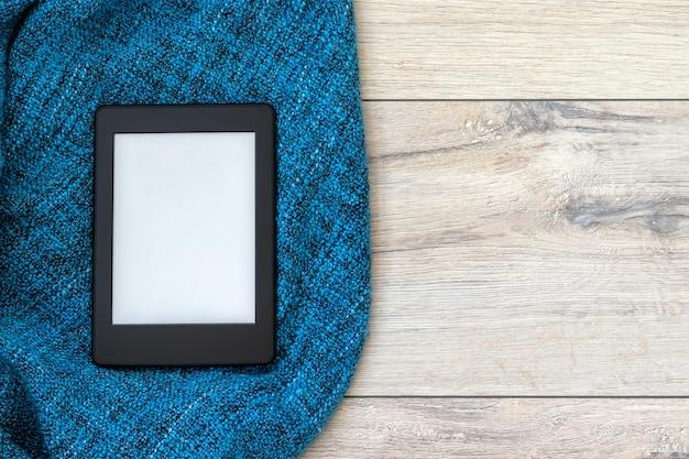 Um livro eletrônico preto moderno com uma tela em branco sobre um cobertor de malha azul brilhante sobre um piso de madeira. tablet de maquete. vista do topo