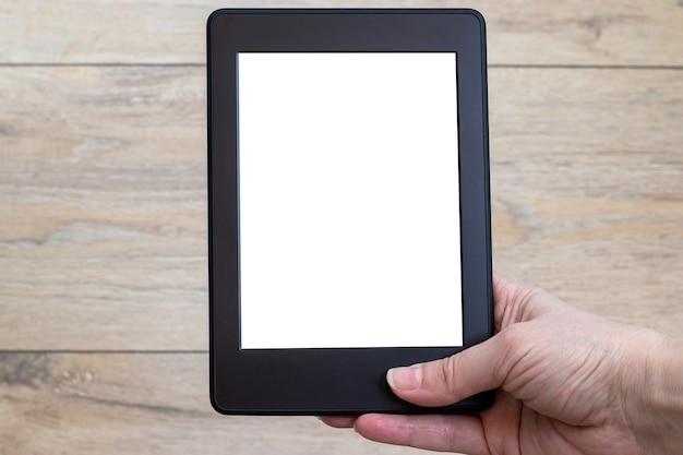 Um livro eletrônico preto moderno com uma tela em branco vazia na mão feminina contra um fundo de madeira borrado. modelo de tablet close up