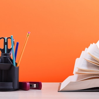 Um livro grande e grosso com as páginas espalhadas como um leque e um suporte com canetas, lápis e tesoura sobre a mesa em um fundo laranja.
