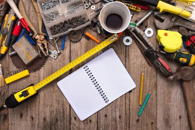 Um local de trabalho empoeirado com ferramentas e um caderno aberto