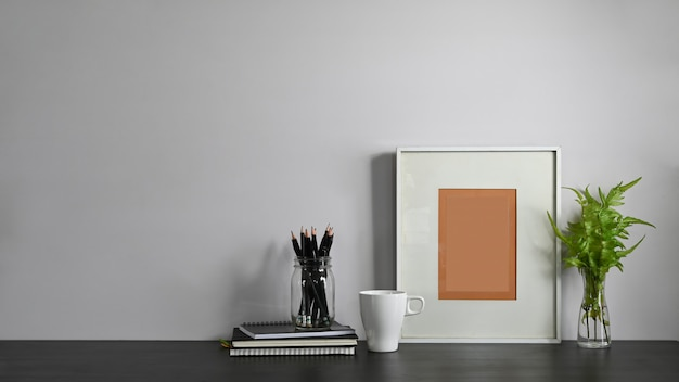 Um local de trabalho organizado é cercado por uma xícara de café, um vaso de lápis e equipamentos de escritório.