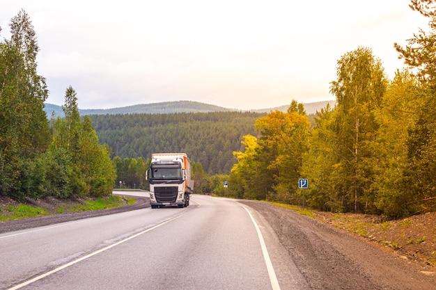 Um longo caminhão percorre a estrada, subindo colina acima, entre montanhas e florestas