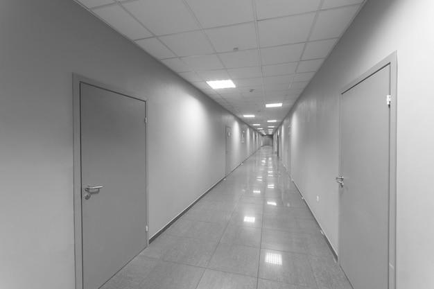 Um longo corredor com portas.