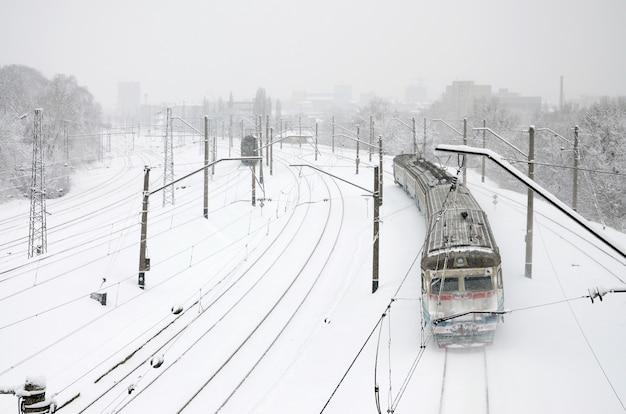 Um longo trem de carros de passageiros está se movendo ao longo da ferrovia