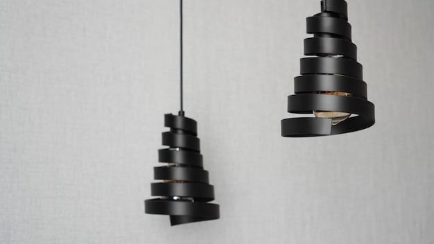 Um lustre moderno feito de espiral de metal preto em um interior branco elegante