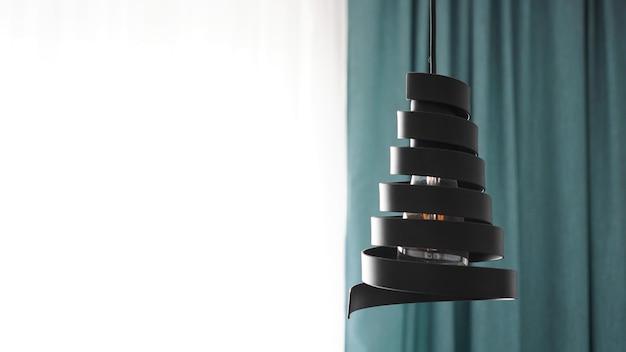 Um lustre moderno feito de espiral de metal preto em um interior elegante em branco e verde
