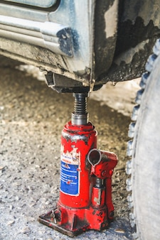 Um macaco vermelho levanta o carro para substituir a roda perfurada.