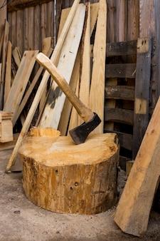 Um machado, cercado por vários tipos de toras, apoiado em uma tábua de cortar. foto de alta qualidade