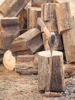 Um machado com uma alça laranja e uma grande pilha de blocos de madeira.