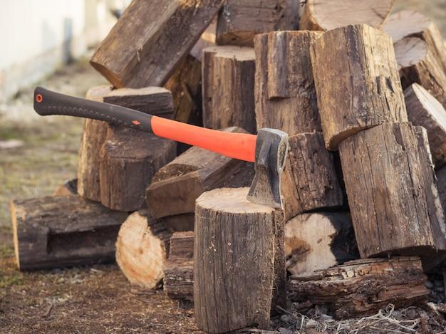 Um machado para colher madeira em um fundo de árvores derrubadas.