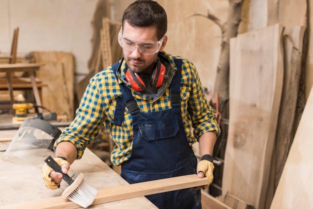 Um, macho, carpinteiro, limpeza, a, prancha madeira, com, escova, em, a, oficina