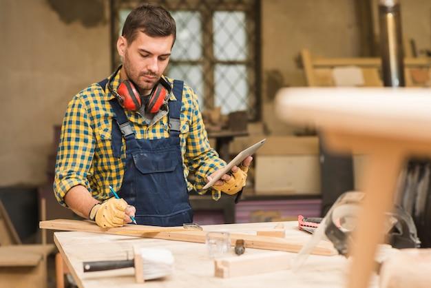 Um, macho, carpinteiro, usando, tablete digital, em, oficina