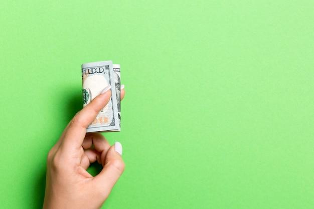 Um maço de cem notas de dólar na mão feminina em fundo colorido. conceito de salário com espaço da cópia