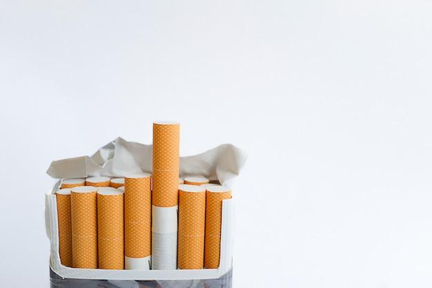 Um maço de cigarros aberto fica na vertical sobre um fundo branco. espaço para texto.
