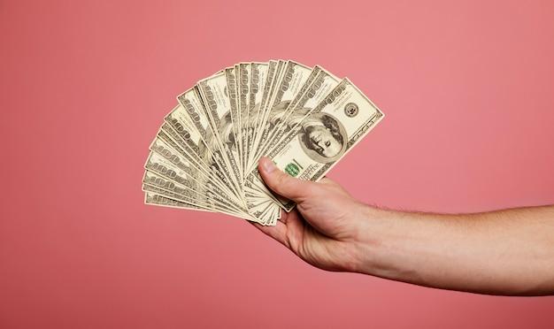 Um maço de dinheiro. a mão de um homem com um monte de dinheiro.