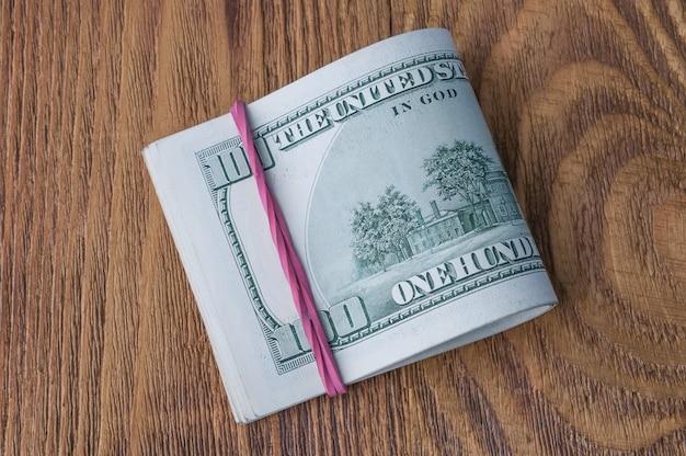 Um maço de notas de cem dólares esticada por um elástico em uma mesa de madeira.