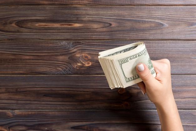 Um maço de notas de cem dólares na mão feminina em fundo de madeira. conceito de salário com espaço da cópia