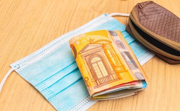 Um maço de notas de euro em uma máscara cirúrgica azul para o conceito de economia durante a terrível pandemia
