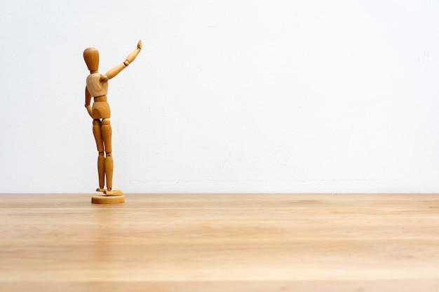 Um manequim boneco de madeira em pose em uma parede branca