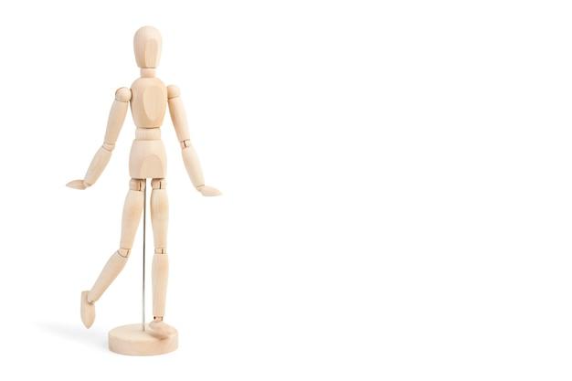 Um manequim de brinquedo de madeira em um fundo branco com espaço de cópia