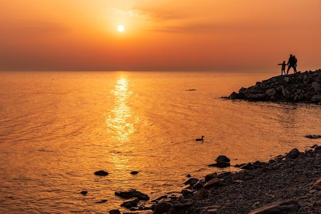 Um mar calmo com um pôr do sol e o sol através das nuvens no céu meditação oceano e céu calma vista do mar o horizonte acima da água
