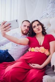 Um marido e uma esposa grávida fazem selfie sentado no sofá. eles se amam. eles estão em casa.