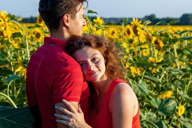 Um marido em pé perto de sua esposa grávida no campo com muitos girassóis em um dia ensolarado.
