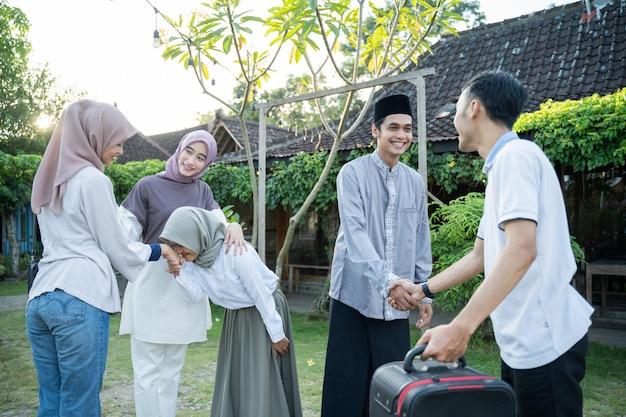 Um marido muçulmano, esposa e filha apertam a mão de sua família quando se encontram