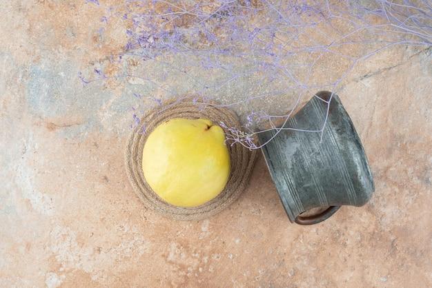 Um marmelo fresco com uma xícara antiga em mármore