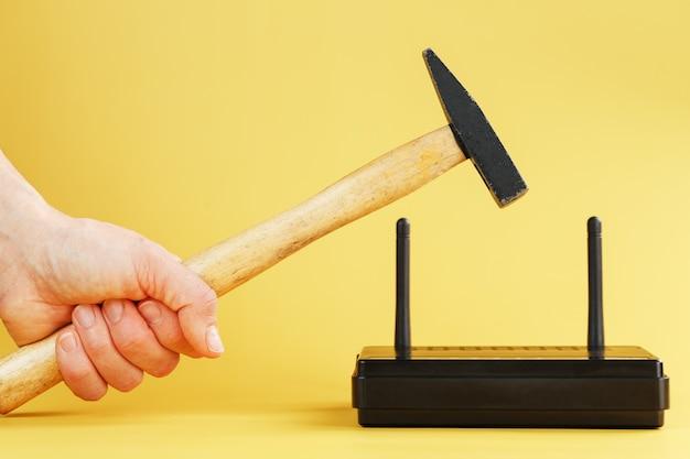 Um martelo atinge o roteador do modem wi-fi para quebrá-lo contra um fundo amarelo.