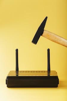 Um martelo atinge o roteador do modem wifi para quebrá-lo contra um fundo amarelo