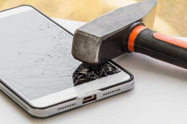Um martelo está no smartphone com uma tela quebrada. o conceito de reparo de eletrônicos.