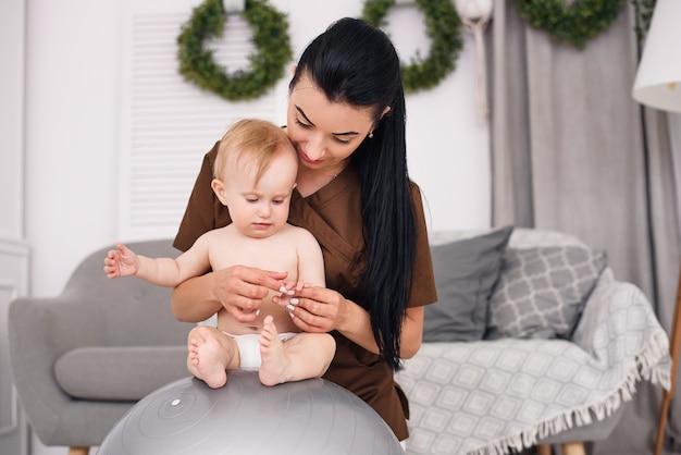 Um massagista profissional feminino com bebê feliz fazendo exercícios com bola de fitness na sala médica. conceito de saúde e médico.