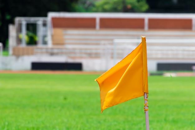 Um mastro de bandeira amarelo pendurado na lateral do campo.