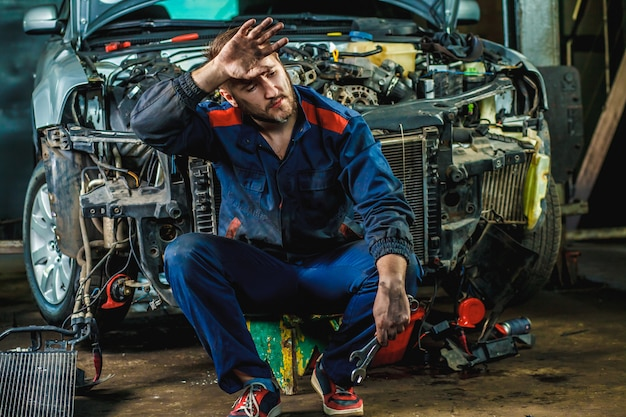 Um mecânico cansado em um traje de proteção azul está sentado perto de um carro desmontado.