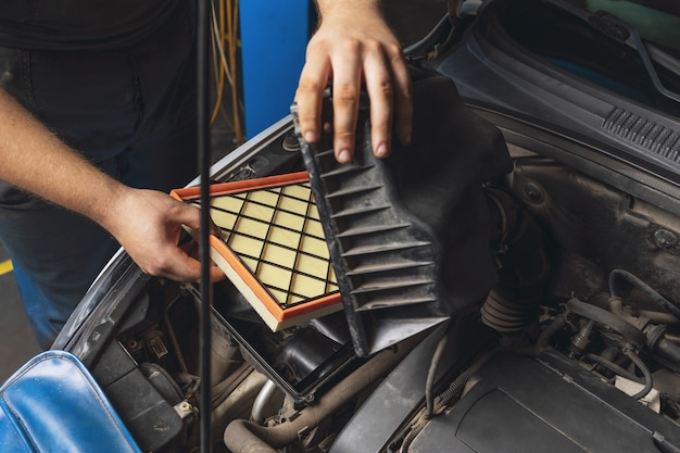 Um mecânico de automóveis instala um novo filtro de ar do motor no carro
