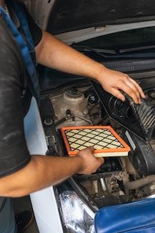 Um mecânico de automóveis instala um novo filtro de ar do motor