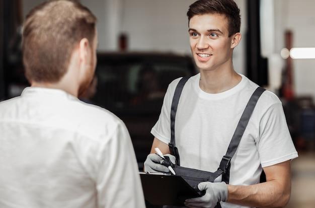 Um mecânico de automóveis sorri para seu cliente e o convida a olhar seu carro.